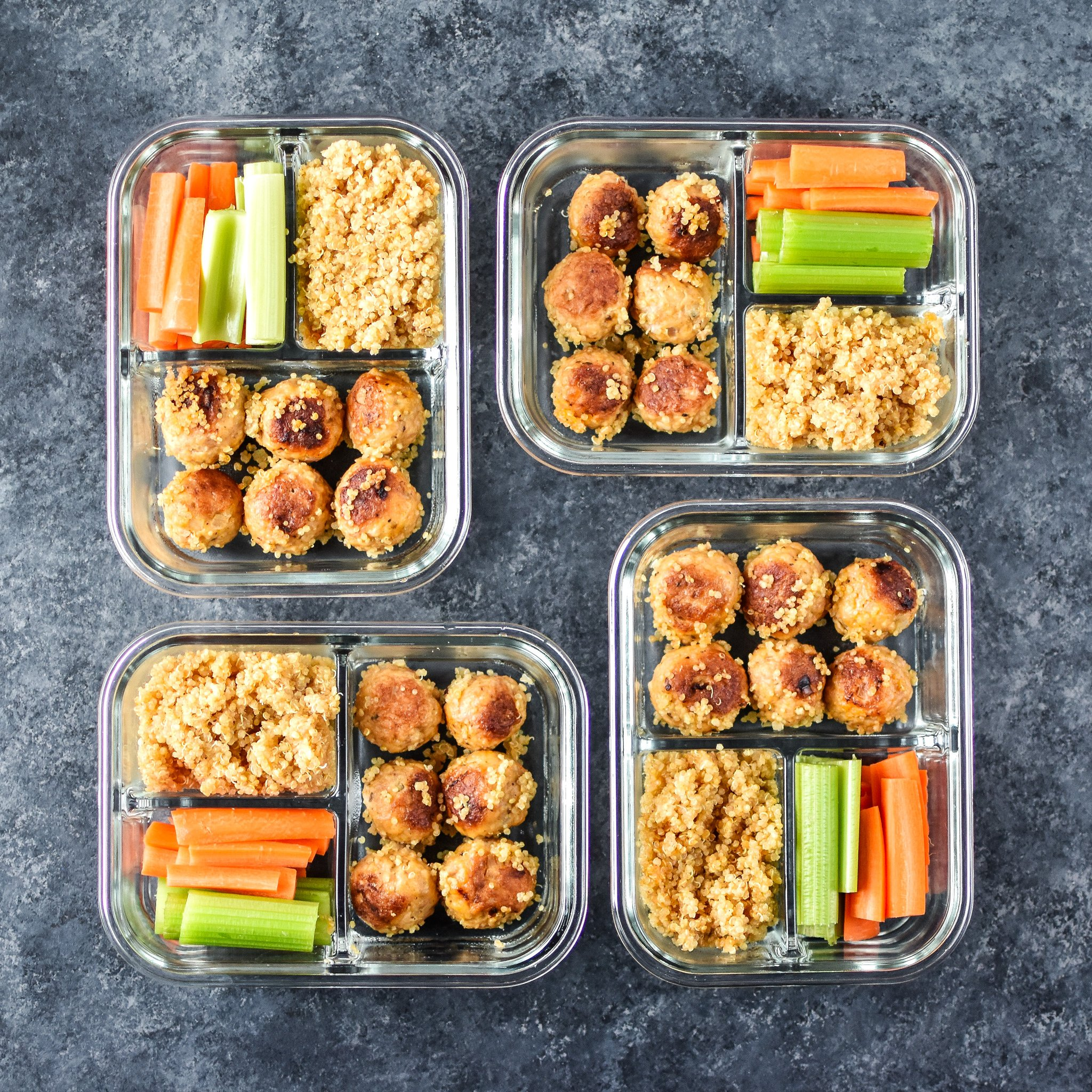 Four meal prep meatballs, quinoa and raw veggies lunches in glass containers.