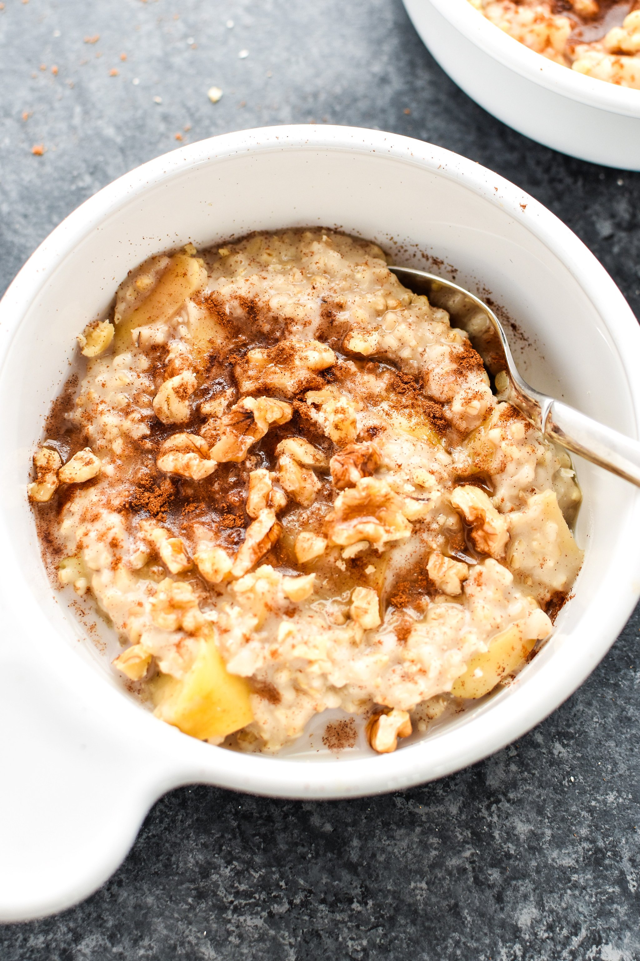 A bowl of cooked oatmeal with apples, cinnamon and walnuts.