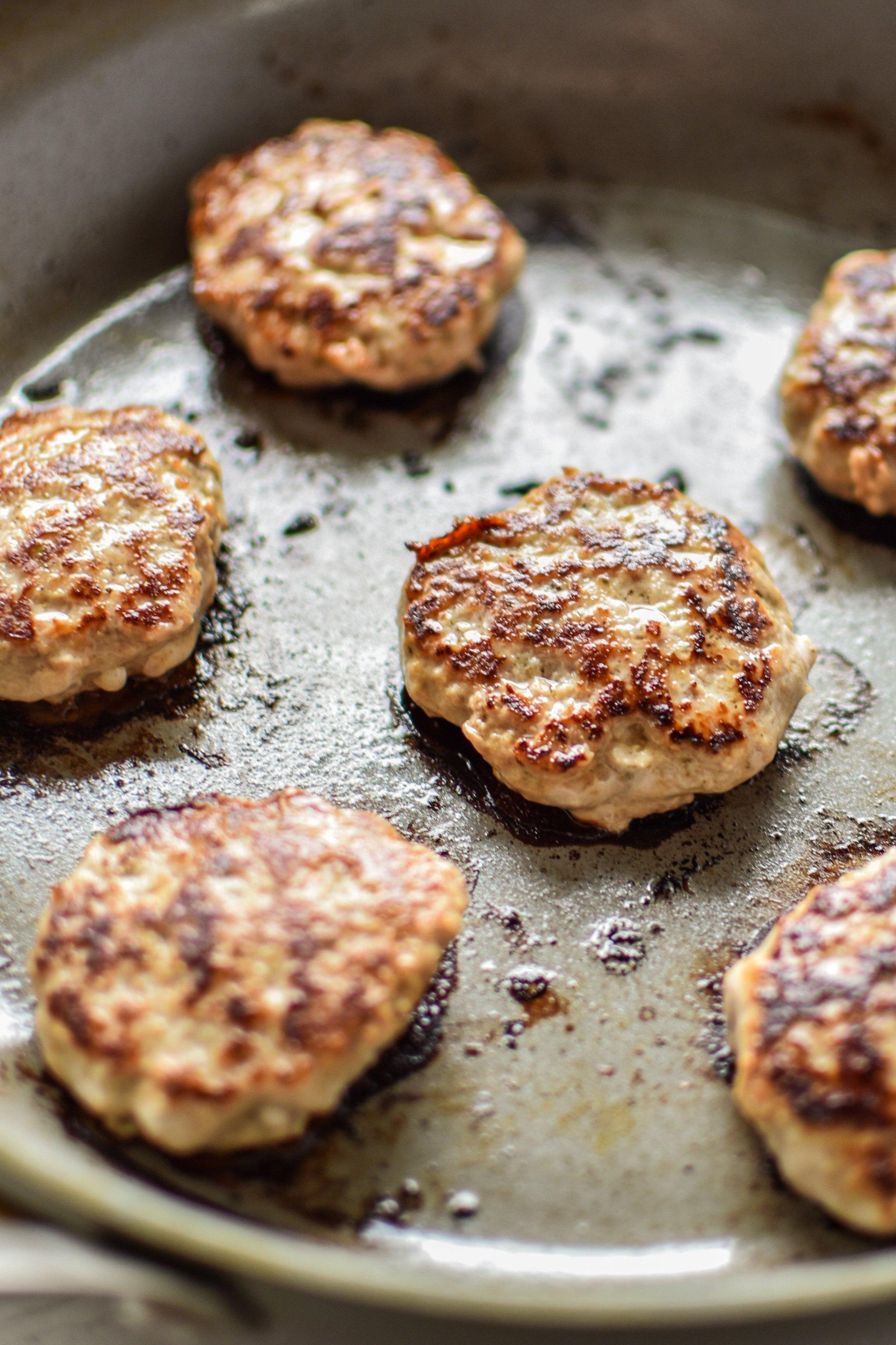 Ground turkey breakfast sausage patties frying in the pan.