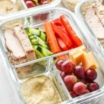 A glass container with chicken, pepper, carrots, cucumber, and more meal prepped for lunch.
