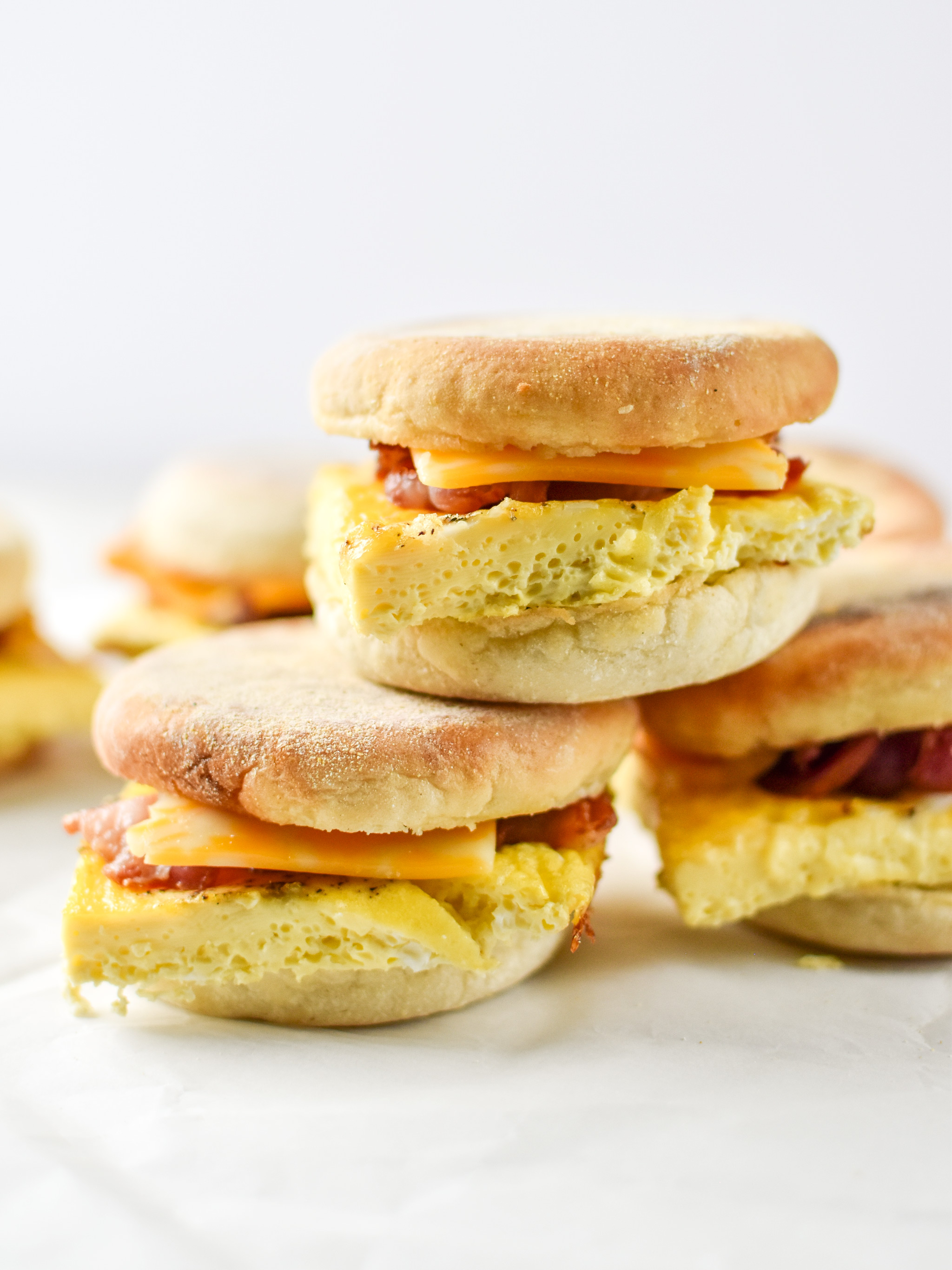 A stack of make-ahead bacon breakfast sandwiches with egg cheese and bacon.