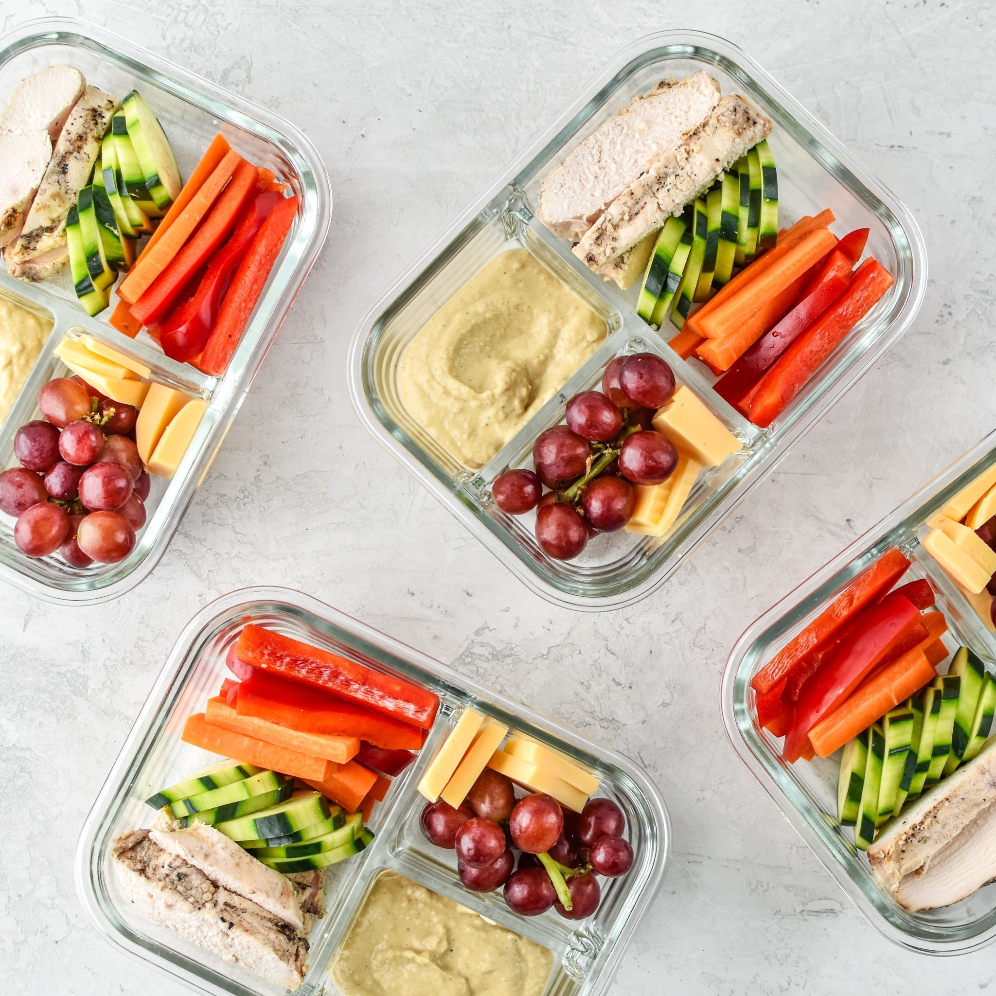 Chicken & hummus place meal prep in 3 compartment containers.