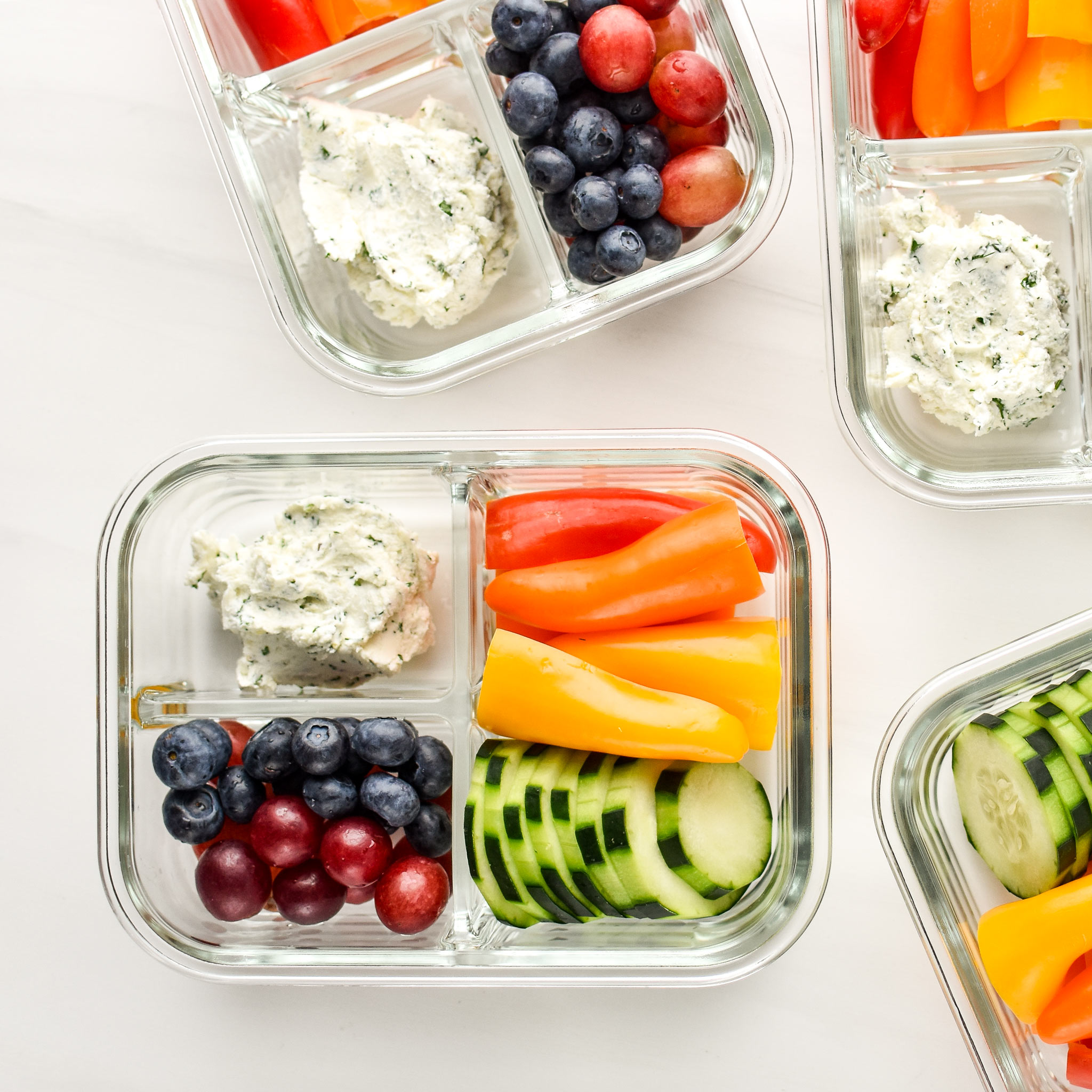 Herbed goat cheese rainbow snack boxes meal prepped in glass containers.