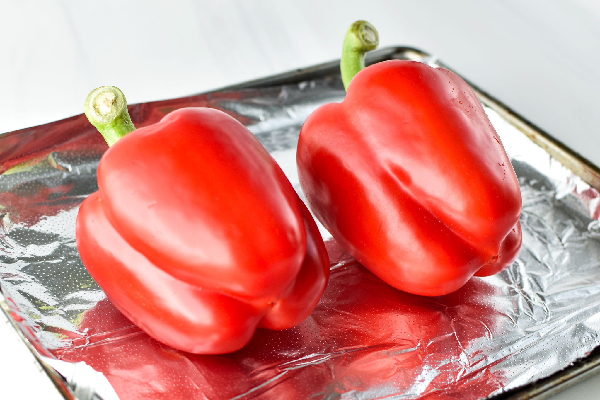 two raw red bell peppers on a sheet pan