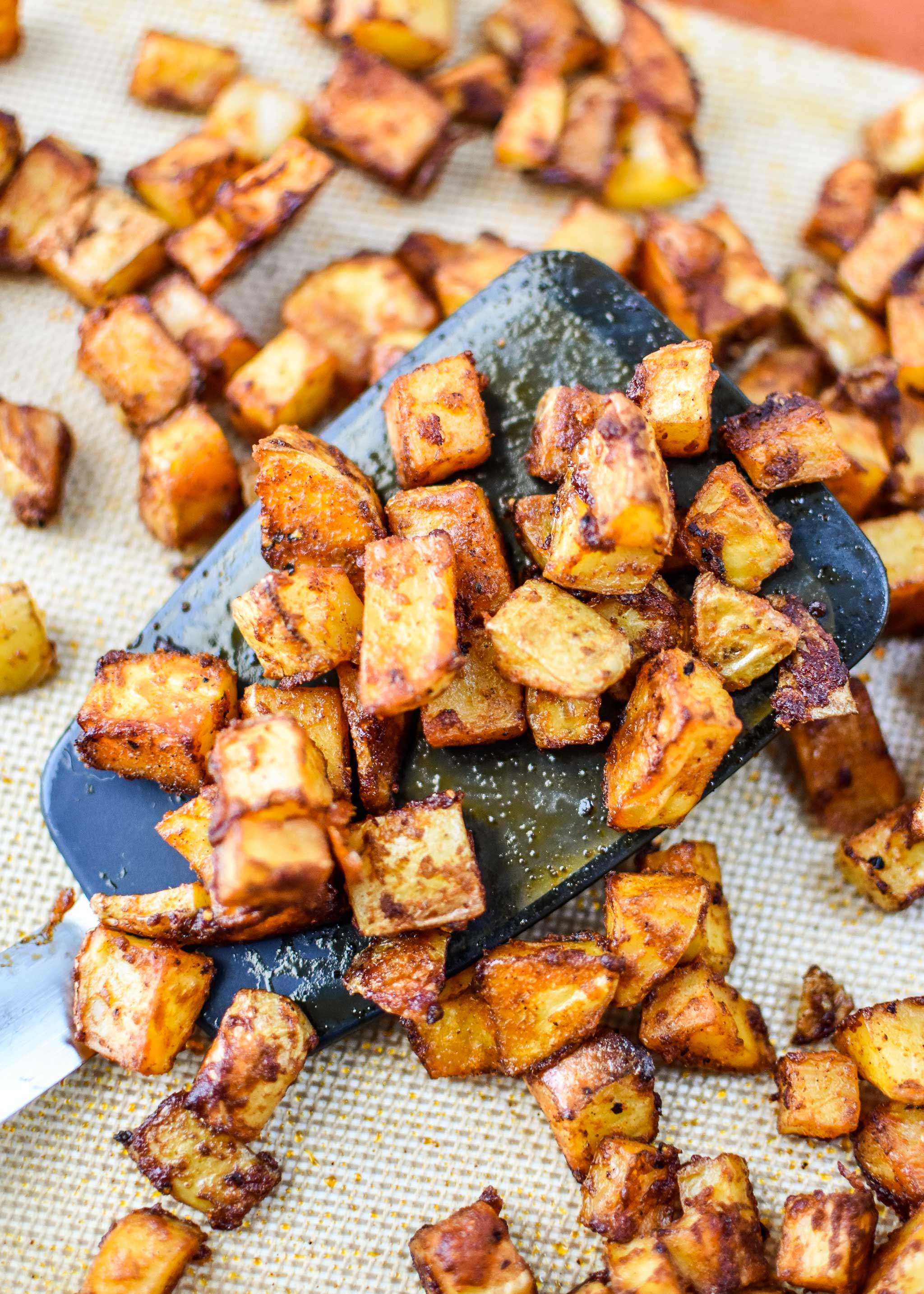 basic oven breakfast potatoes on a sheet pan with a spatula