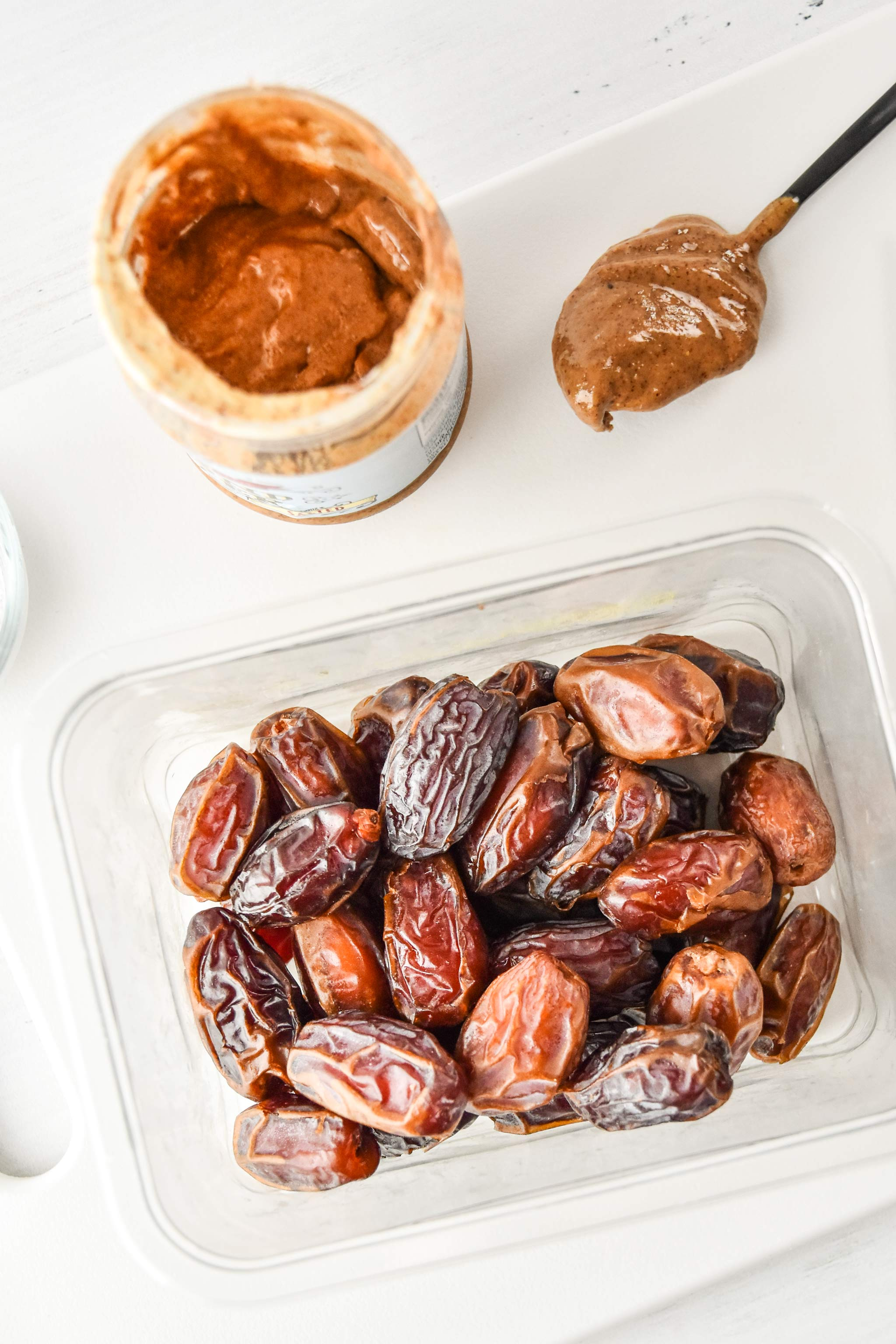 medjool dates and some almond butter on a cutting board