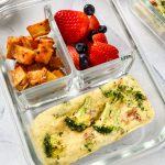 Broccoli bacon mini frittata in a meal prep container with potatoes and berries