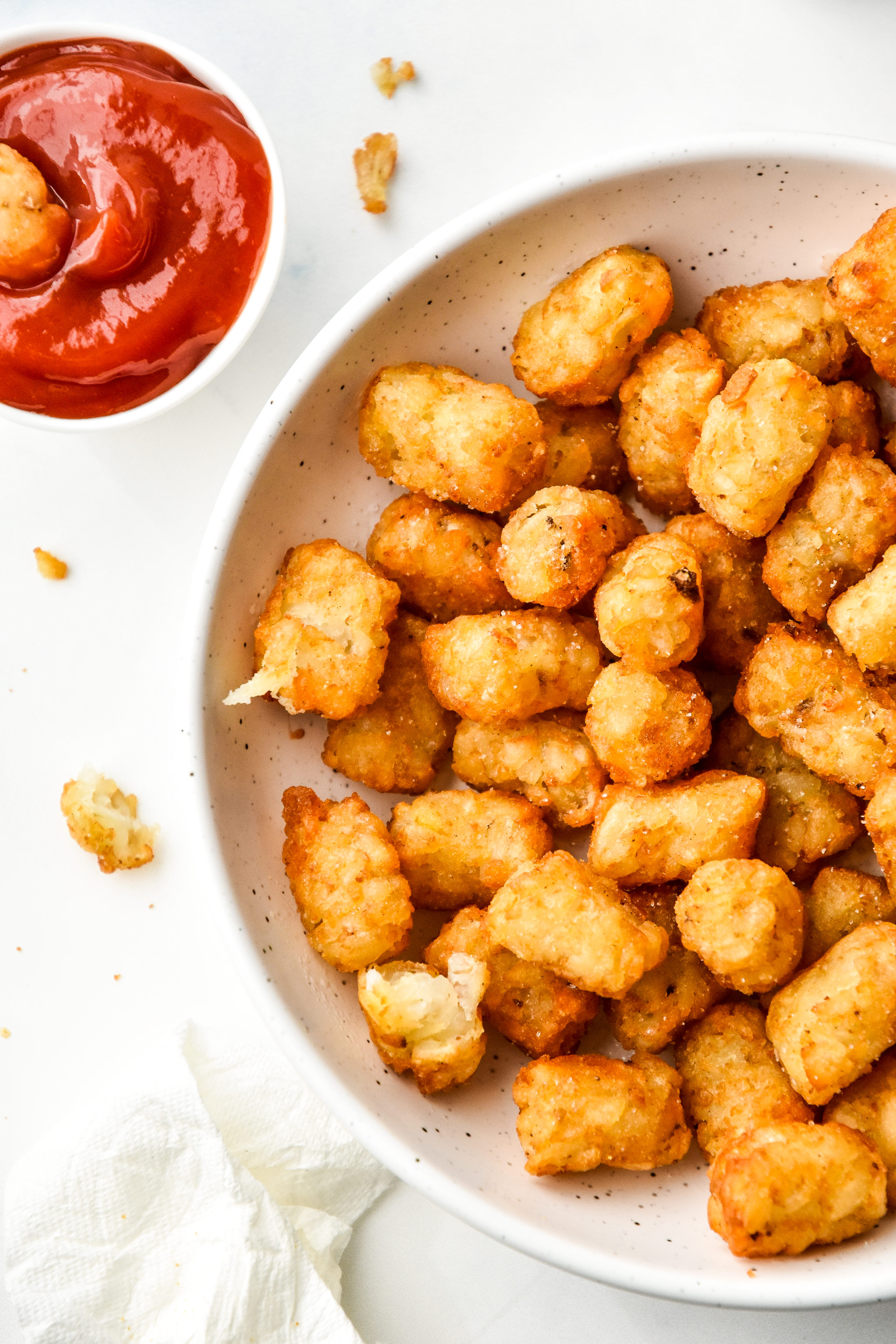 tater tots cooked in an air fryer served with ketchup in a bowl